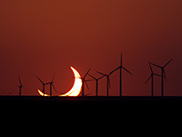 Partial solar eclipse with windmills